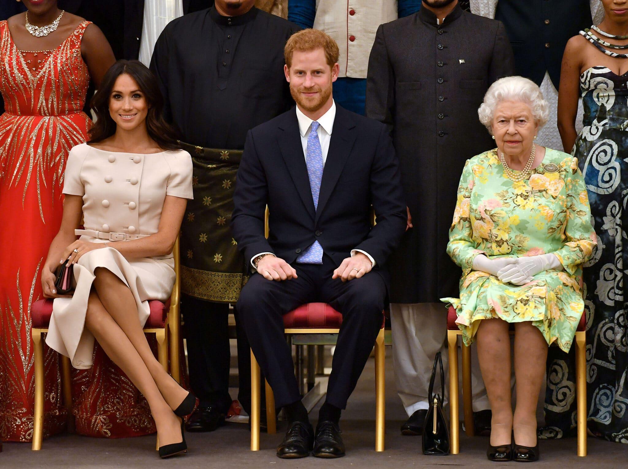 Královna Alžběta, princ Harry a jeho manželka Meghan