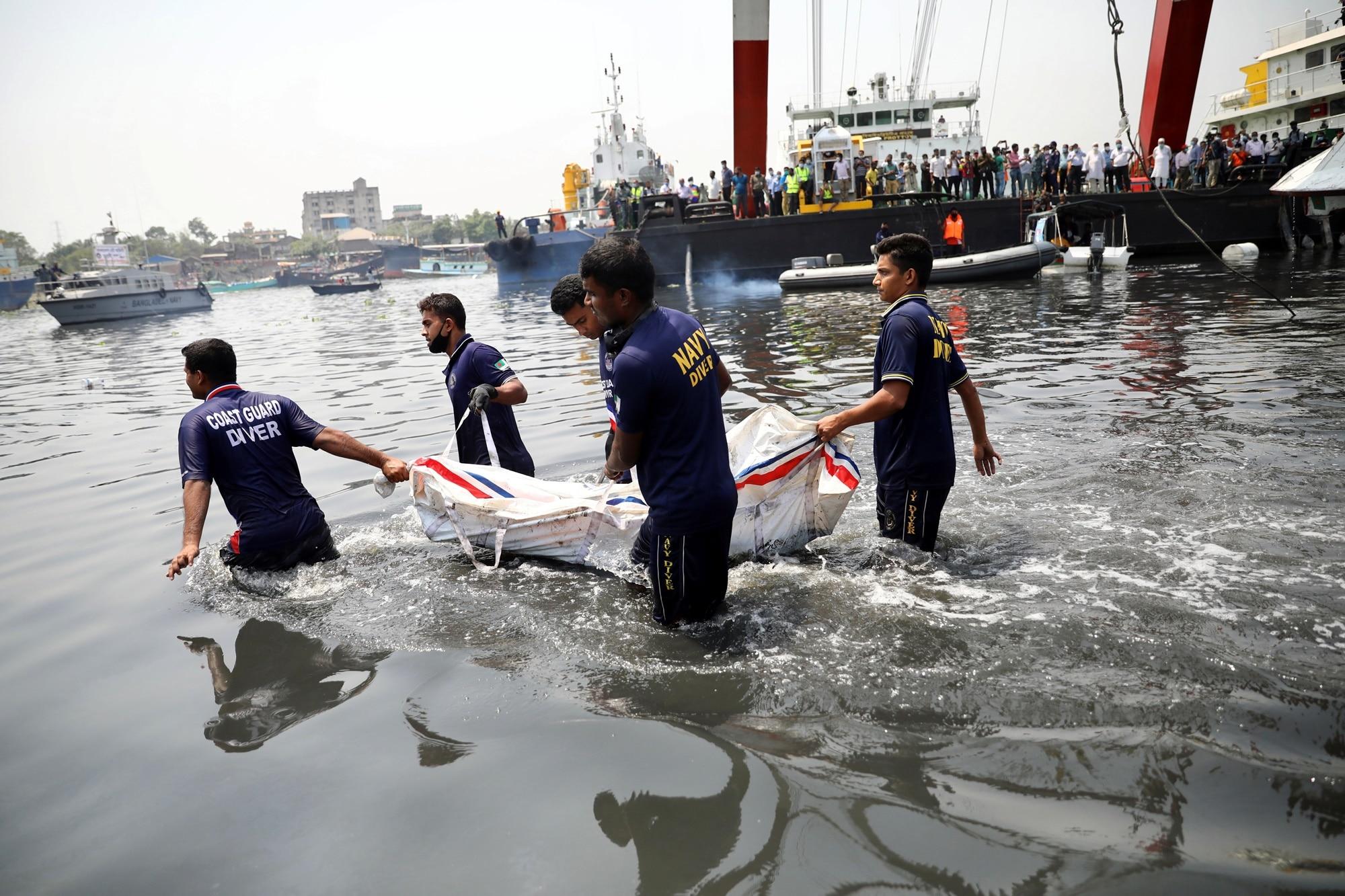 Záchranáři nesou tělo nalezené po nehodě