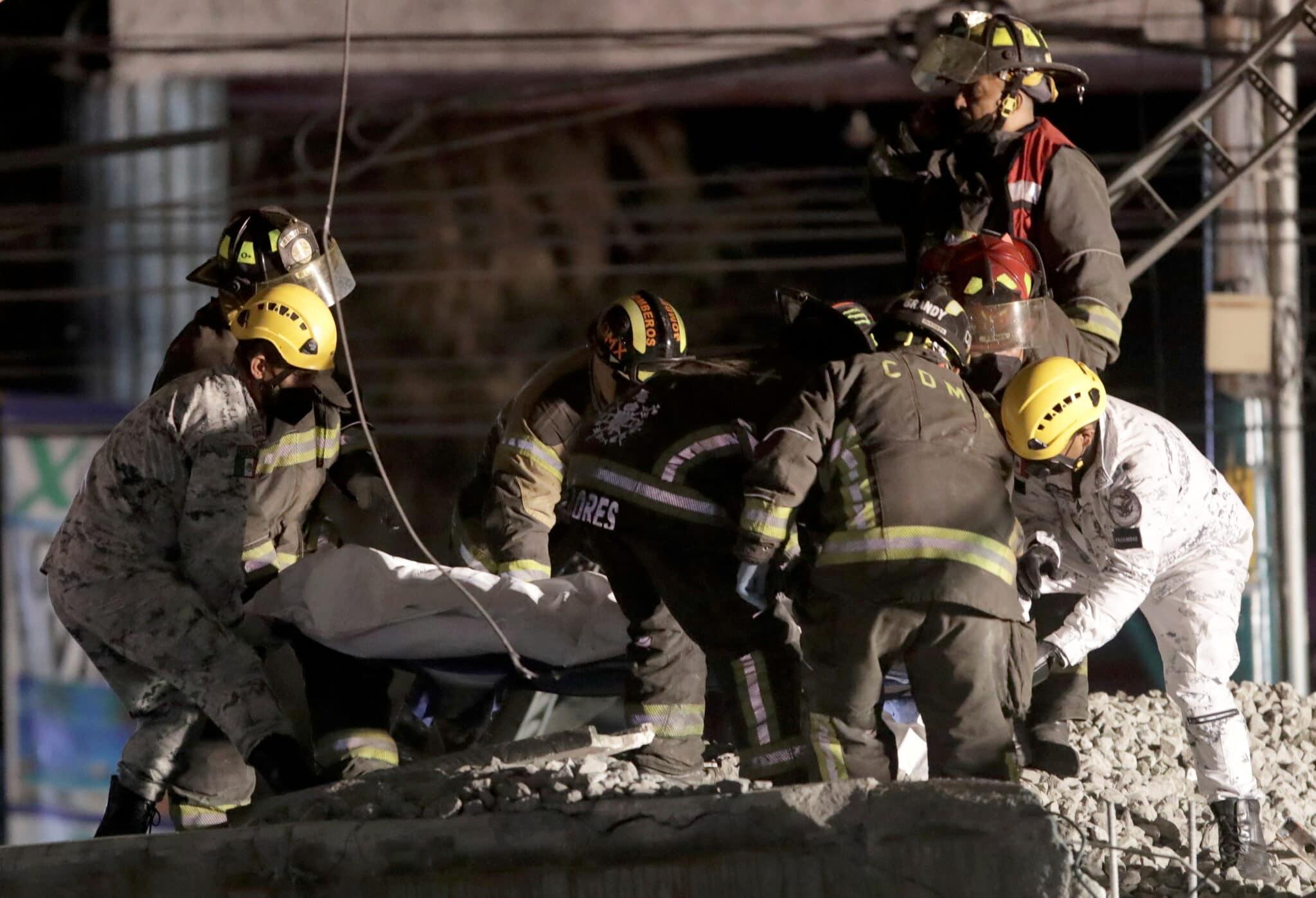 Záchranáři nesou tělo jedné z obětí