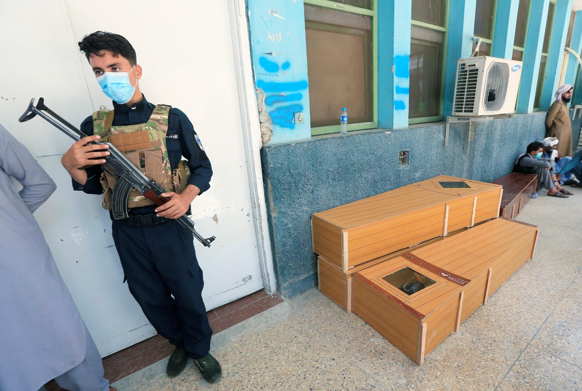 Afghánský policista u rakví připravených pro zastřelené zdravotníky