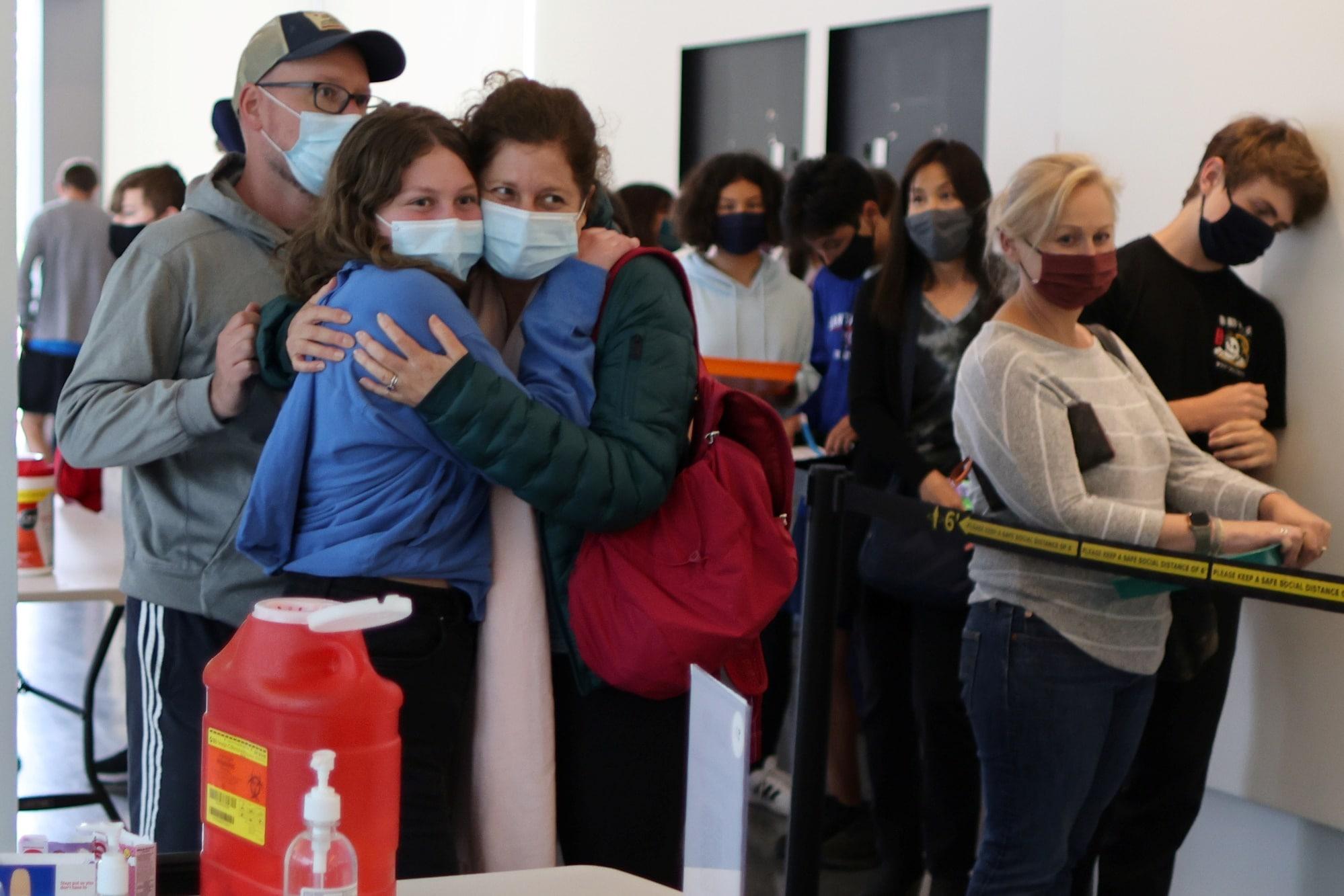 Kalifornie: Žena objímá dceru poté, co se obě nechaly očkovat proti covidu-19