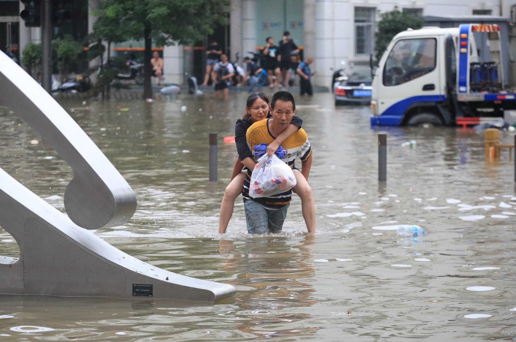 Lidé se brodí zatopenými ulicemi