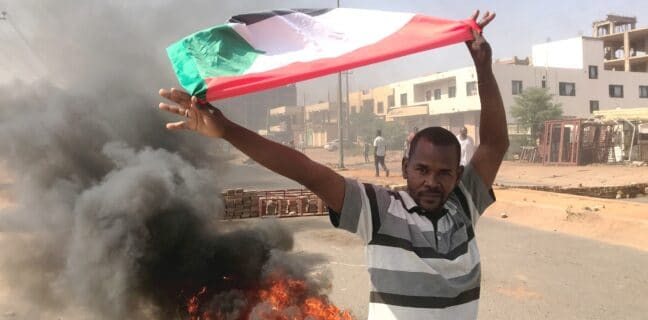 Demonstrant v Chartúmu mává vlajkou